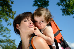 A little girl in a baby carrier walks with his mom. In nature Stock Image