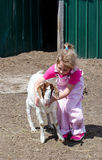 Little girl with baby goat on the farm Royalty Free Stock Images