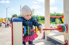 Little girl baby in the hat with a flower and a blue denim jacket and a red dress playing in the playground and smiling Stock Photography