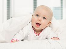Little Girl Baby Laying Under White Blanket Stock Photo