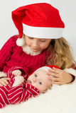 Little girl with baby lie in the hats of Santa Claus. Focus on a baby royalty free stock image