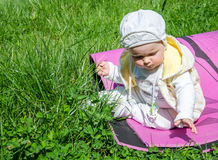 Little girl baby playing in the grass in a meadow sitting on karemat Royalty Free Stock Image