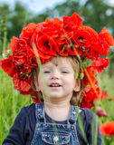 Little girl baby playing happy on the poppy field with a wreath, a bouquet of color A red poppies and white daisies, wearing a den Royalty Free Stock Images
