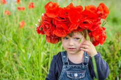 Little girl baby playing happy on the poppy field with a wreath, a bouquet of color A red poppies and white daisies, wearing a den Royalty Free Stock Image