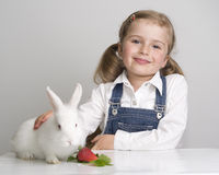 Little girl and baby rabbit Stock Images