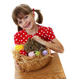 Little girl with baby rabbit and easter eggs Stock Image