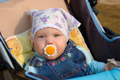 Little girl with baby's dummy sit in carriage. Pretty little girl with baby's dummy sit in carriage. In kerchief and jeans catsuit Stock Photos