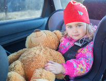 Little girl , baby in a safety car seat. Royalty Free Stock Photography