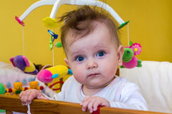 Little girl baby sitting in her bed Stock Photo