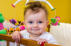 Little girl baby smiling sitting in her bed Royalty Free Stock Photos