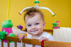 Little girl baby smiling sitting in her bed Stock Image