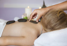 Little girl back receiving hot stone massage Royalty Free Stock Photo