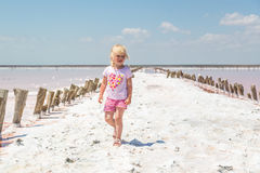 Little girl on the background of salt lakes of the dead sea and pink rose Stock Photos