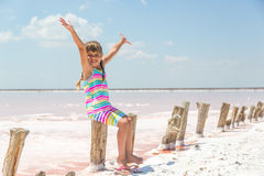 Little girl on the background of salt lakes of the dead sea and pink rose, raised her hands up Royalty Free Stock Photo