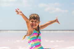 Little girl on the background of salt lakes of the dead sea and pink rose, raised her hands up Royalty Free Stock Photography