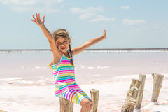 Little girl on the background of salt lakes of the dead sea and pink rose, raised her hands up Stock Photography