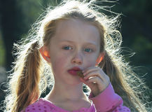 A Little Girl with Backlit Hair Eating a Cookie Royalty Free Stock Image