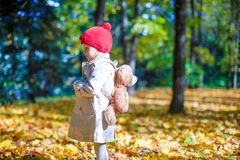 Little girl with a backpack-bear walks in the Royalty Free Stock Photo