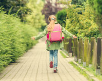 Little girl with a backpack going to school Royalty Free Stock Images