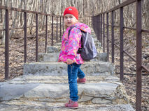 Little girl with a backpack going up the stairs. Royalty Free Stock Photography