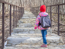Little girl with a backpack going up the stairs. stock photos