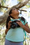 Little girl with backpack holding dslr camera in her hand looking up in the sky on a sunny day. In the forest Royalty Free Stock Images