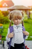 Little girl with a backpack near the school royalty free stock photography