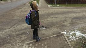 Little girl with backpack after school try to cross the road. In winter day stock video footage
