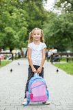 Little girl with a backpack in the schoolyard. The concept of school, study, education, childhood.  royalty free stock image