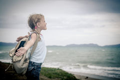 Little girl with a backpack standing on the beach Stock Photo
