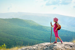 Little girl with backpack standing on cliff edge Stock Image