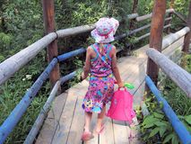 Little girl with backpack goes on old wooden bridge. Little girl with backpack and toys going to beach on wooden bridge Royalty Free Stock Photos