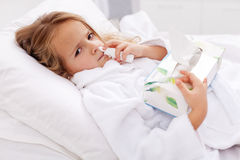 Little girl with bad cold - using nasal spray Royalty Free Stock Photography