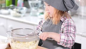 Little girl baker adds flour for dough for cheesecakes. Close up stock footage