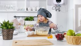 Little girl baker adds flour for dough for cheesecakes. Close up stock video