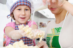 Little baker cooking in kitchen with mother. Little girl in baker hat and apron cooking in kitchen with mother stock photography