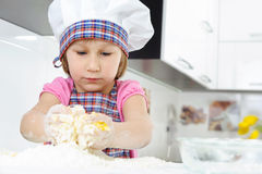Little girl in baker hat cooking Royalty Free Stock Photo