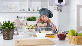 Little girl baker on kitchen puts eggs to the pastry dough for cooking biscuits. Close up stock footage