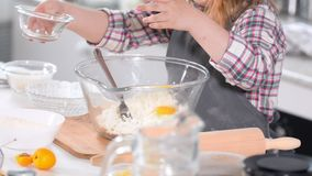 Little girl baker on kitchen puts eggs to the pastry dough for cooking biscuits. Close up stock video