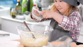 Little girl baker on kitchen puts sugar to the pastry dough for cooking biscuits. Close up stock footage