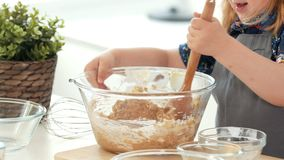 Little girl baker kneading the dough big wooden spoon. Close up stock footage