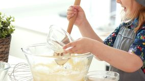 Little girl baker puts the ingredients for kneading the dough. Close up stock video footage