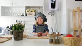 Little girl baker rolls out the dough and talking. Close up stock footage