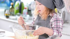 Little girl baker taste the cookie dough. Close up stock video footage