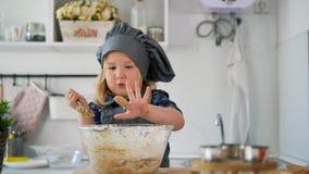 Little girl baker taste the cookie dough. Close up stock video