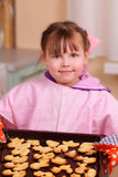 Little girl bakes biscuits Stock Photos