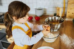 Little girl baking a cake in the kitchen. royalty free stock images
