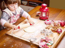 Little girl baking Christmas cookies cutting pastry Stock Photos