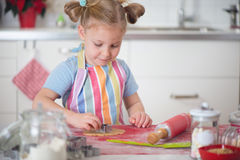 Little girl baking Christmas cookies at home Royalty Free Stock Images