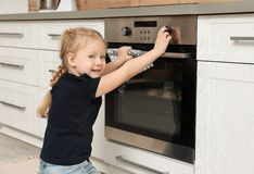 Little girl baking cookies in oven stock photography